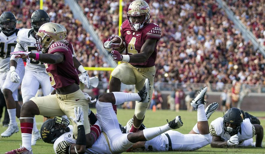 FILE - In this Saturday, Oct. 15, 2016, photo, Florida State running back Dalvin Cook runs against Wake Forest in the first half of an NCAA college football game in Tallahassee, Fla. Cook and Clemson quarterback Deshaun Watson have the potential to make a move in a nationally televised night game, but the pressure is really on Washington quarterback Jake Browning. (AP Photo/Mark Wallheiser)