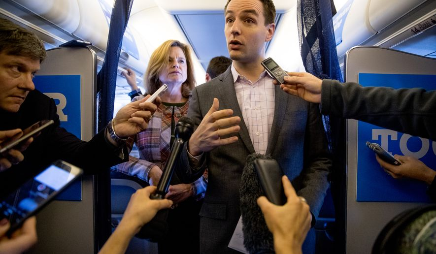 Campaign Manager Robby Mook, right, accompanied by Director of Communications Jennifer Palmieri, left, speaks to members of the media aboard Democratic presidential candidate Hillary Clinton's campaign plane, Friday, Oct. 28, 2016, while traveling to Iowa. (AP Photo/Andrew Harnik)