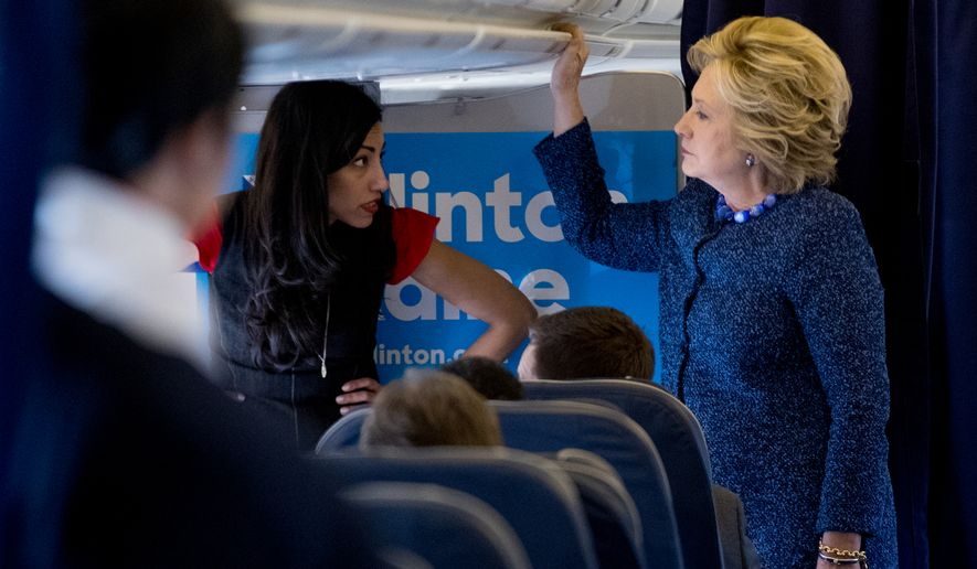 Democratic presidential candidate Hillary Clinton speaks with senior aide Huma Abedin, left, aboard her campaign plane at Westchester County Airport in White Plains, N.Y., Friday, Oct. 28, 2016, before traveling to Iowa for rallies. (AP Photo/Andrew Harnik) ** FILE **