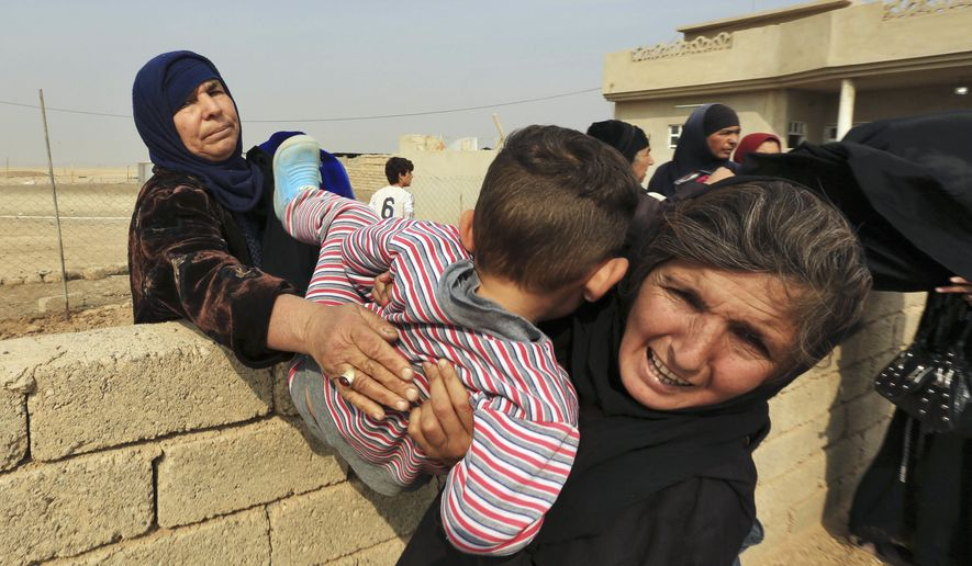Women carry a boy over a wall as civilians flee their houses in the village of Tob Zawa, Iraq, about 9 kilometers (5.6 miles) from Mosul, Tuesday, Oct. 25, 2016, as Iraq's elite counterterrorism forces fight against Islamic State militants. (AP Photo/Khalid Mohammed)