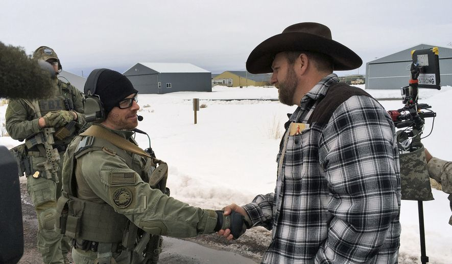 In this Jan. 22, 2016, file photo, Ammon Bundy, right, shakes hand with a federal agent guarding the gate at the Burns Municipal Airport in Burns, Ore. The stunning acquittal of seven people who occupied a federal bird refuge in Oregon as part of a Western land dispute was a rejection of the prosecutions conspiracy case, not an endorsement of the armed protest, a juror said Friday, Oct. 28, 2016.  (AP Photo/Keith Ridler, File).