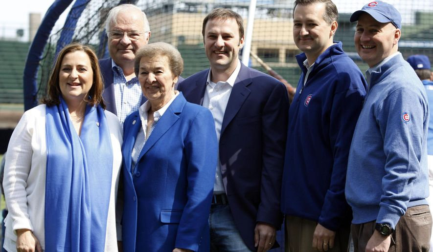 FILE - In this April 12, 2010 file photo, Chicago Cubs owner Tom Ricketts, second from right, and family members pose on the field before the Chicago Cubs baseball home opener against the Milwaukee Brewers in Chicago. From left are Cubs board member Laura Rickets, Joe Ricketts, Marlene Ricketts, board member Todd Ricketts, board Chairman Tom Ricketts and board member Pete Rickets. Most of the Ricketts family who own the Chicago Cubs who are playing in the World Series are Republicans who are supporting Republican Donald Trump. Daughter Laura Ricketts, meanwhile, is a top Democratic donor who held a high-dollar fundraiser for Hillary Clinton this summer and was a super delegate for her to the Democratic National Convention. (AP Photo/Nam Y. Huh, File)