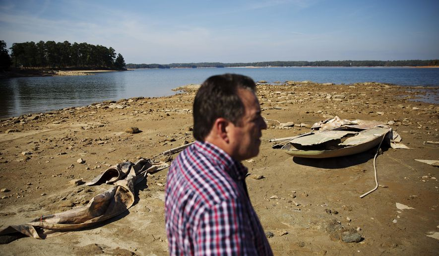 In this Wednesday, Oct. 26, 2016 photo, a sunken boat is exposed by receding water levels on Lake Lanier as U.S. Army Corps of Engineers Natural Resources Manager Nick Baggett looks on in Flowery Branch, Ga. Some of the South's most beautiful mountains and valleys this fall are filled with desperation, as a worsening drought kills crops, threatens cattle and sinks lakes to their lowest levels in years. (AP Photo/David Goldman)