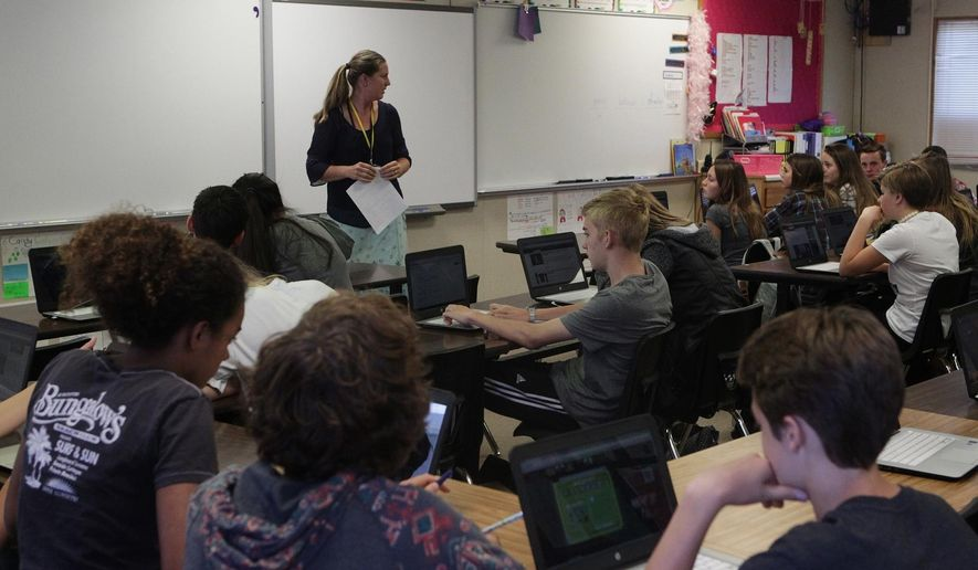 FILE - In this May 27, 2016, file photo, Junction Elementary School substitute teacher Molly Goodman teaches an eighth-grade class at the school in Redding, Calif.  California voters are deciding whether to approve $9 billion in bonds for school and community college construction projects _ a measure proponents say is necessary to fill a backlog of needed new buildings and renovations.   (Andreas Fuhrmann/Record Searchlight via AP, File)