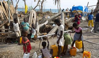 In this Oct. 25, 2016 photo, children collect drinking water from a station set up by Swiss Humanitarian Aid, in Aux Coteaux, a district of Les Cayes, Haiti. Wells and piped networks that people depend on for clean water across the country's southern peninsula were contaminated or damaged by a combination of ocean storm surge and sewage from the overflowing latrines that are commonly used in rural Haiti. (AP Photo/Dieu Nalio Chery)