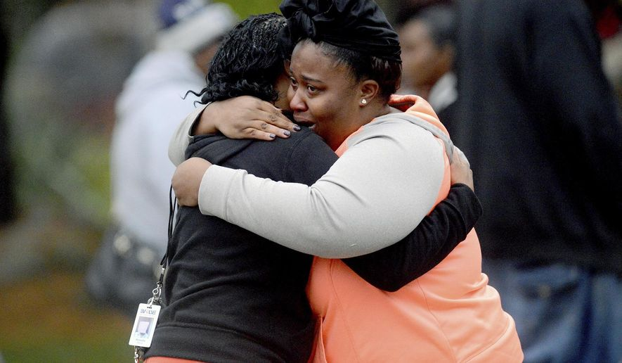 Two women embrace at the scene of a double murder suicide Friday, Oct. 28, 2016, in Lansing, Mich. (Dave Wasinger/Lansing State Journal via AP)
