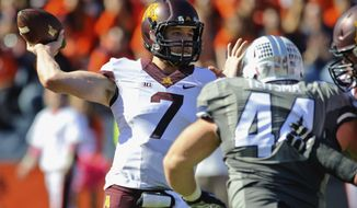 In this Oct. 25, 2014, photo, Minnesota quarterback Mitch Leidner (7) throws the ball while under pressure from Illinois defensive lineman Austin Teitsma (44) during an NCAA football game at Memorial Stadium in Champaign, Ill.  In a rebuilding season for Illinois, even the homecoming opponent is coming to town with a winning record and payback on its mind. In 2014 the Illini upset a Golden Gophers team that competing for a Big Ten West title, winning 28-24 on a late touchdown. Minnesota quarterback Mitch Leidner says it was one of the first things coach Tracy Claeys stressed this week. (AP Photo/Bradley Leeb)
