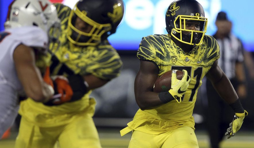 FILE - In this Sept. 10, 2016, file photo, Oregon running back Royce Freeman, right, runs against Virginia during the second half of an NCAA college football game in Eugene, Ore. With a five-game losing streak, Oregon, who plays Arizona State in Eugene, Ore., Saturday, Oct. 29, 2016, is in danger of missing out on a bowl game for the first time since 2004. (AP Photo/Chris Pietsch, File)