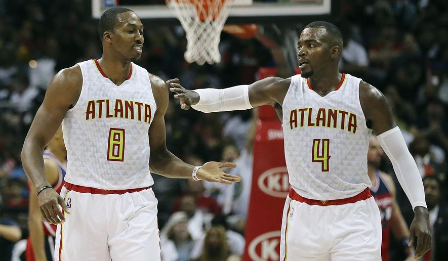 FILE - In this Thursday, Oct. 27, 2016, file photo, Atlanta Hawks' Dwight Howard and Paul Millsap exchange high fives pulling away from the Washington Wizards in the final minutes of a 114-99 victory during the fourth period in the home opener of an NBA basketball game in Atlanta. One of the most intriguing storylines of the NBA season could be in Atlanta, where Howard and the Hawks are hoping they'll be just what the other needs to recapture what they once had.  (Curtis Compton/Atlanta Journal-Constitution via AP, File)