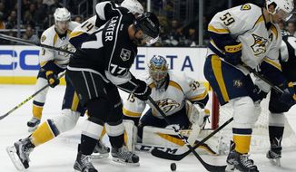 Los Angeles Kings center Jeff Carter (77) shot is stopped by Nashville Predators goalie Pekka Rinne, center, of Finland, with defenseman Mattias Ekholm (14), of Sweden, and defenseman Roman Josi (59), of Switzerland, defending during the second period of an NHL hockey game in Los Angeles, Thursday, Oct. 27, 2016. (AP Photo/Alex Gallardo)