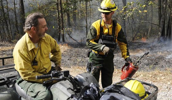 Alabama Forestry Commission firefighters Jim Junkin, left, and Brad Lang talk about strategies for fighting a wildfire near Brookside, Ala., on Thursday, Oct. 27, 2016. Wildfires are burning hundreds of acres of land daily across the South amid a drought. (AP Photo/Jay Reeves)