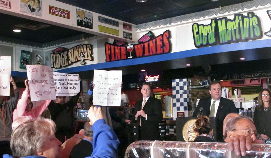 New Jersey Gov. Chris Christie, right, looks away as protesters disrupt his speech in Seaside Heights N.J. on Friday Oct. 28, 2016. Christie marked the upcoming four-year anniversary of the Oct. 29, 2012 storm by visiting a boardwalk bar that was damaged by it, but protesters from Sandy victim advocacy groups shouted him down, forcing him to stop speaking for about five minutes before resuming his remarks. (AP Photo/Wayne Parry)