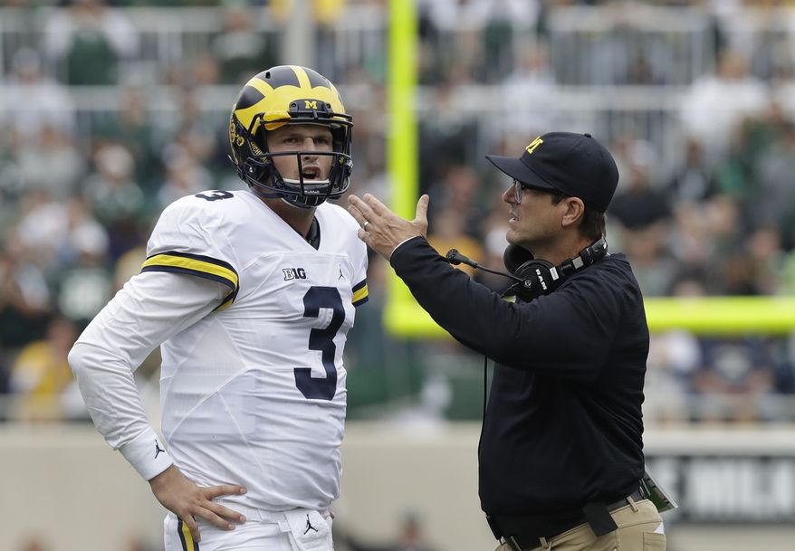 Michigan head coach Jim Harbaugh talks with quarterback Wilton Speight (3) during the first half of an NCAA college football game against Michigan State, Saturday, Oct. 29, 2016, in East Lansing, Mich. (AP Photo/Carlos Osorio)