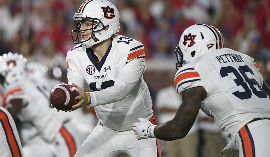 Auburn quarterback Sean White (13) hands off the ball to running back Kamryn Pettway (36) during the first quarter of an NCAA college football game against Auburn in Oxford, Miss., Saturday, Oct. 29, 2016. (AP Photo/Thomas Graning)