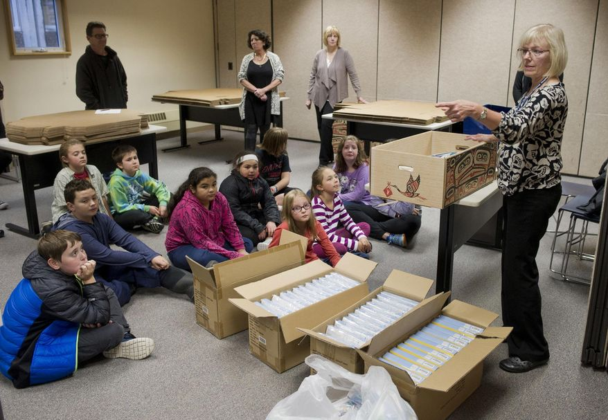 Karen White, right, Director of Bartlett Regional Hospital Obstetrics Department gives instructions to students from Faith Community School before they ensemble baby boxes for new mothers Sept. 22, 2016, at Bartlett Regional Hospital in Juneau, Alaska. The box, covered in an intricate Alaska Native design, is one of the hundreds of baby boxes Bartlett Regional Hospital Foundation is supplying mothers who give birth at the hospital. (Michael Penn/Juneau Empire via AP)