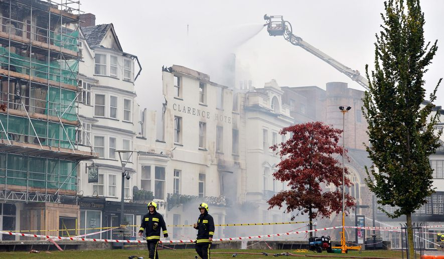 Firefighters continue to tackle the blaze at the badly damaged The Royal Clarence Hotel, in Exeter, England, Saturday, Oct. 29, 2016. A fire has severely damaged what is thought to be England's oldest hotel. The blaze in the southwestern city of Exeter raced through the historic Royal Clarence Hotel, which overlooks the city's medieval cathedral. Firefighters were still tackling the blaze on Saturday, a day after it broke out. The hotel, which had been operating under the name Abode Exeter, dates to 1769. (Ben Birchall/PA via AP)