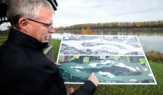 ADVANCE FOR WEEKEND EDITIONS OCT. 29-30 - In this Oct. 20, 2016 photo, Tim Cowman, natural resources administrator with the South Dakota Geological Survey, shares information about Goat Island across the Missouri River at Brooky Bottom boat ramp near Wynot, Neb. Its ownership long disputed, Goat Island will now be managed by the National Park Service. (Justin Wan/Sioux City Journal via AP)