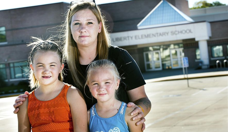 ADVANCE FOR SATURDAY, OCT. 29, 2016- In this Sept. 19, 2016 photo, Desiree Navin poses for a photo with her daughters from left, Joeyanna and Jayceelynn, in front of Liberty Elementary School in Sioux City, Iowa. Navin open-enrolled her daughters into a different school across town after she discovered a registered sex offender was living nearby Liberty. Like many others on the registry, the offender is allowed to live there due to changes in state law seven years ago. (Justin Wan/Sioux City Journal via AP)