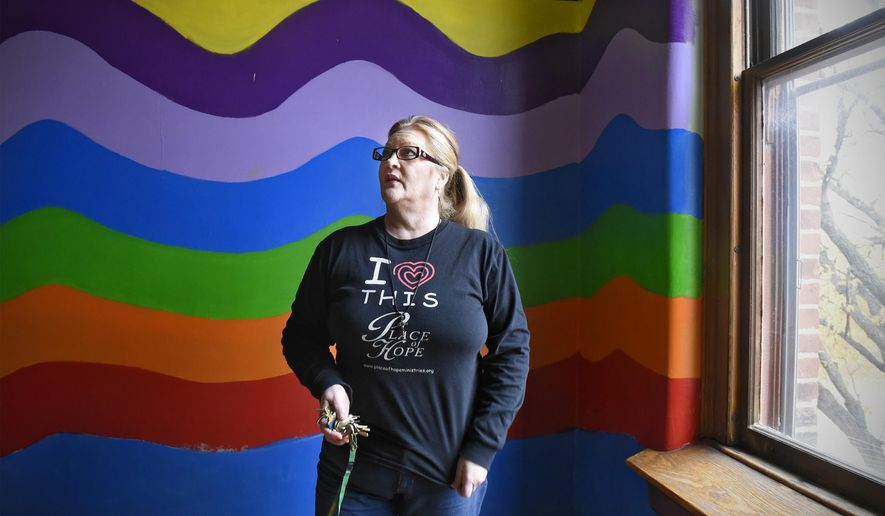 In this Tuesday, Oct. 25, 2016 photo, The Rev. Carol Smith is surrounded by brightly-colored paint while talking about renovations in a children's room on a newly-renovated floor of the Place of Hope Ministries building in St. Cloud, Minn. (Dave Schwarz /St. Cloud Times via AP)