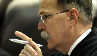 FILE - In this Wednesday, Sept. 21, 2016 file photo, Chief Justice Lawton Nuss questions counsel during arguments in a school funding case at the Kansas Supreme Court in Topeka, Kan. Nuss is one of four Kansas Supreme Court justices facing a campaign to oust them in the Nov. 8, 2016 election say the court has decided capital murder cases on legal and constitutional issues while avoiding politics and emotion. (AP Photo/Charlie Riedel, File)