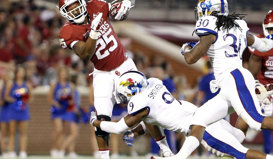 Oklahoma running back Joe Mixon (25) is tackled by Kansas safety Fish Smithson (9) during the first half of an NCAA college football game in Norman, Okla., Saturday, Oct. 29, 2016. (AP Photo/Alonzo Adams)