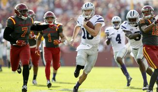 Kansas State quarterback Jesse Ertz, center, runs from Iowa State's Willie Harvey, left, and Jay Jones, right, during the first half of an NCAA college football game, Saturday, Oct. 29, 2016, in Ames, Iowa. (AP Photo/Charlie Neibergall)