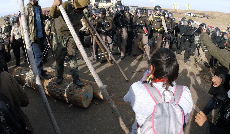 FILE--In this Oct. 27, 2016, file photo, protesters in the left foreground shield their faces as a line of law enforcement officers holding large canisters with pepper spray shout orders to move back during a standoff in Morton County, N.D. On the same day seven defendants celebrated acquittal in Portland, Ore., for their armed takeover of a federal wildlife refuge in Oregon, nearly 150 protesters camped out in North Dakota to protest an oil pipeline were arrested. (Mike McCleary/The Bismarck Tribune via AP, file)