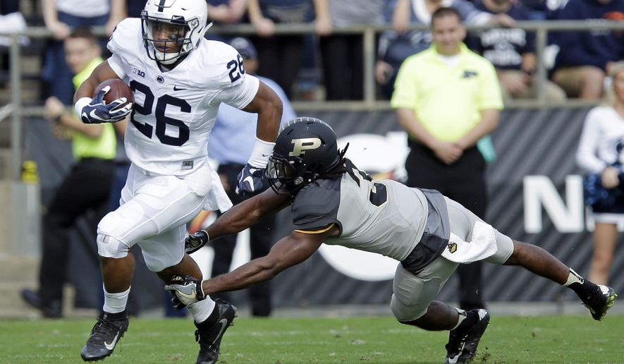 Penn State running back Saquon Barkley (26) breaks the tackle of Purdue safety Leroy Clark (3) during the first half of an NCAA college football game in West Lafayette, Ind., Saturday, Oct. 29, 2016. (AP Photo/Michael Conroy)
