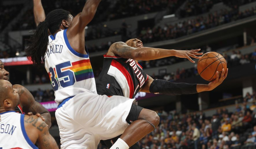 Denver Nuggets forward Kenneth Faried, left, blocks Portland Trail Blazers guard Damian Lillard on a drive during the first half of an NBA basketball game Saturday, Oct. 29, 2016, in Denver. (AP Photo/David Zalubowski)