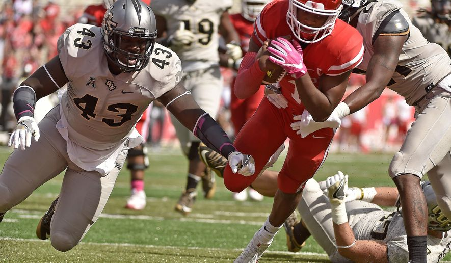 Houston quarterback Greg Ward Jr., center, breaks the tackles of Central Florida defensive lineman Aaron Cochran, left, and defensive back Drico Johnson, right, to score the go-ahead touchdown during the second half of an NCAA college football game, Saturday, Oct. 29, 2016, in Houston. Houston won 31-24. (AP Photo/Eric Christian Smith)