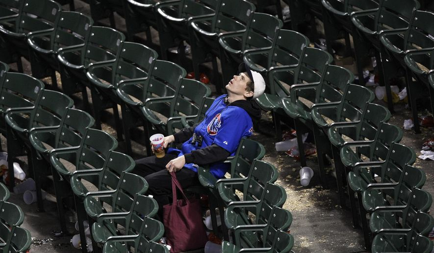 FILE - In this Oct. 2, 2008, file photo, a Chicago Cubs fan sits alone in the stands after Game 2 of the NL Division Series against the Los Angeles Dodgers in Chicago. What happens when a lovable loser is no longer a loser? If the Cubs win the World Series for the first time since 1908, what happens to fans who have waited for next year their entire lives? Experts in psychology suggest that Cubs fans will undergo a big change in their identity, which has been shaped by more than a century of falling short of winning the World Series. (AP Photo/Charles Rex Arbogast, File)