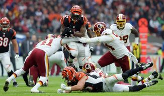 Cincinnati Bengals running back Jeremy Hill (32) is tackled by Washington Redskins free safety Will Blackmon (41) during an NFL Football game between Cincinnati Bengals and Washington Redskins at Wembley Stadium in London, Sunday Oct. 30, 2016. (AP Photo/Tim Ireland)