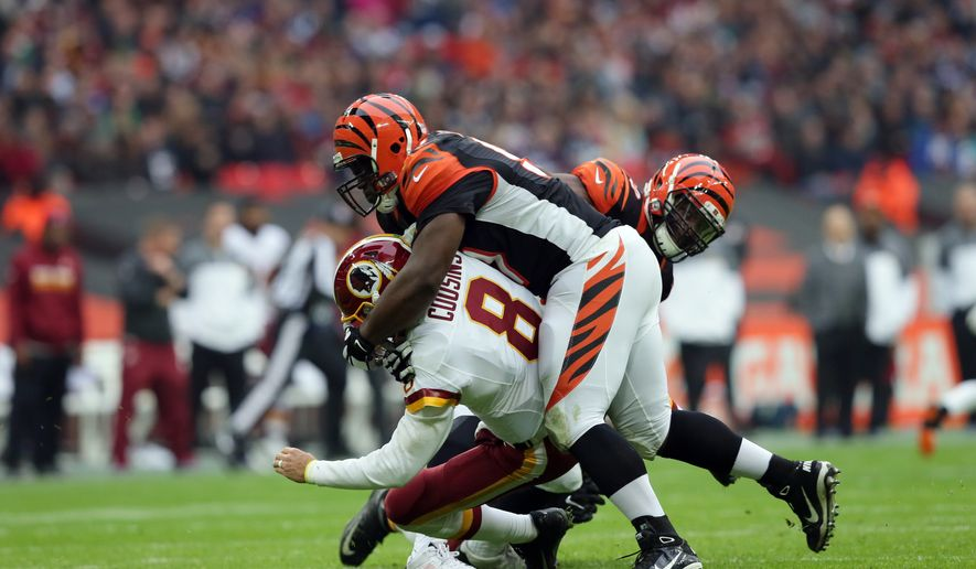 Washington Redskins quarterback Kirk Cousins (8) is sacked by Cincinnati Bengals defensive tackle Geno Atkins (97) during an NFL Football game between Cincinnati Bengals and Washington Redskins at Wembley Stadium in London, Sunday Oct. 30, 2016. (AP Photo/Tim Ireland)