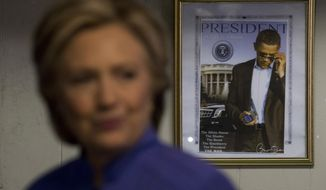 A photograph of President Barack Obama hangs on the wall behind Democratic presidential candidate Hillary Clinton as she greets people at Betty's Soul Food Restaurant in Fort Lauderdale, Sunday, Oct. 30, 2016. (AP Photo/Andrew Harnik)
