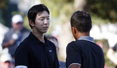 Seung-Yul Noh, left, of South Korea, congratulates Xander Schauffele after completing the Sanderson Farms Championship golf tournament, Sunday, Oct. 30, 2016, in Jackson, Miss. (AP Photo/Rogelio V. Solis)