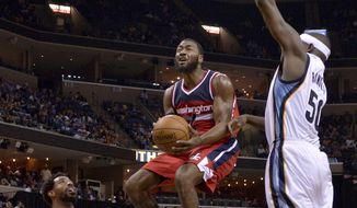Washington Wizards guard John Wall (2) shoots between Memphis Grizzlies guard Mike Conley (11) and forward Zach Randolph (50) in the first half of an NBA basketball game, Sunday, Oct. 30, 2016, in Memphis, Tenn. (AP Photo/Brandon Dill)