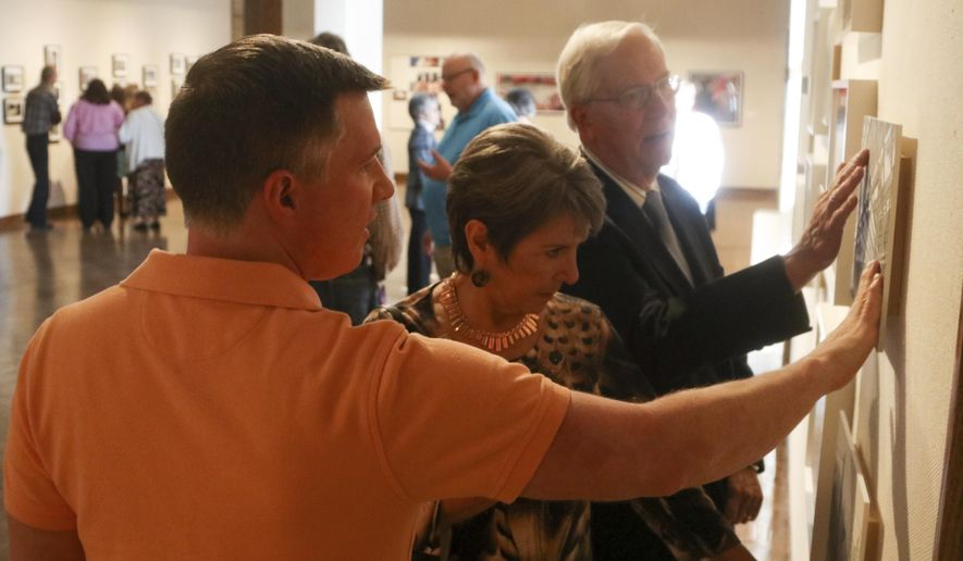 ADVANCE FOR MONDAY OCT 31 AND THEREAFTER - In this Sunday Oct. 23, 2016 photo, Executive Director of the Huntington Museum of Art, Geoffrey K. Fleming, from left, Sue Richardson and Bob Bowen touch pieces of art during Sight Unseen at the Huntington Museum of Art in Huntington, W.Va. Sight Unseen: International Photography by Blind Artists will be shown at the Huntington Museum of Art from Oct. 15, 2016, through Jan. 8, 2017. (Anthony Davis/The Herald-Dispatch via AP)
