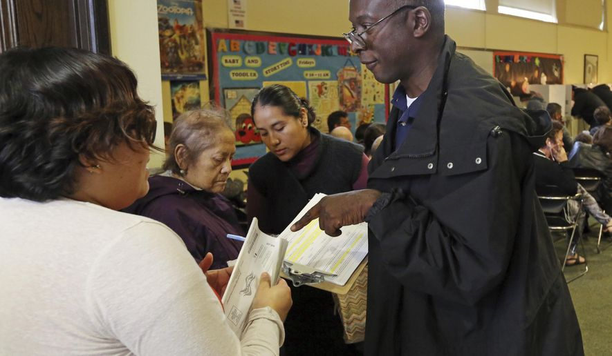 Poll worker Phillip George helps a voter check in at a weekend early voting polling place at the North Hollywood branch library in Los Angeles on Sunday, Oct. 30, 2016. Los Angeles County election officials say some voters waited more than two hours to cast a ballot amid strong interest in early voting. Mike Sanchez, a spokesman for the Los Angeles County Registrar-Recorder, said Sunday that people waited for more than two hours during peak times Saturday at weekend voting centers that opened in and Culver City, Calif. (AP Photo/Reed Saxon)