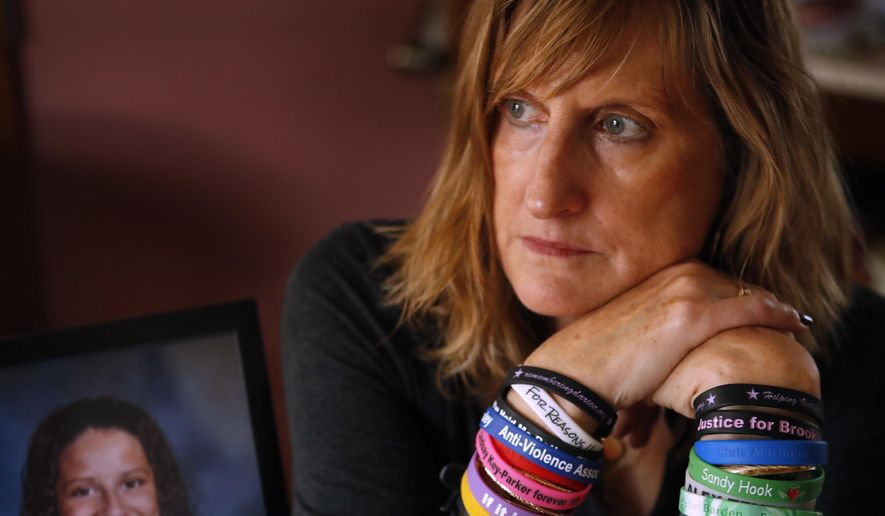 Judi Richardson, a citizen sponsor of a ballot initiative to require background checks for gun buyers, wears wrist bands bearing the names and places of victims of gun violence, at her home in South Portland, Maine, on Wednesday, Oct. 26, 2017. Richardson's daughter Darien, in photo at left, died after being shot by an intruder in her apartment in 2010 in Portland, Maine. (AP Photo/Robert F. Bukaty)