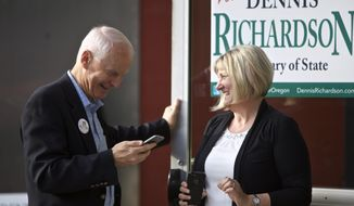 FILE--In this May 17, 2016, file photo, Oregon Republican Secretary of State candidate Dennis Richardson, left, and his wife Cathy Richardson take a phone call during a primary election night gathering for supporters in Portland, Ore. With a Republican threatening to take a state-wide office for the first time in many years in Oregon, the battle for secretary of state has become the hottest state race. (AP Photo/Craig Mitchelldyer, file)