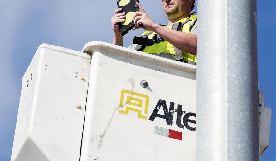 Technician Jeremy Hoegemeyer uses a tablet to share the view from the top of a street light with his manager as they determine precise traffic camera positioning on Oct. 20, 2016 in Lincoln, Neb.  In order to help equipment laden city worker sort out personal and private use of government-owned devices, city leaders recently released new regulations that cover the use of iPads, other tablets, cellphones and smartphones. (Kristin Streff /The Journal-Star via AP)