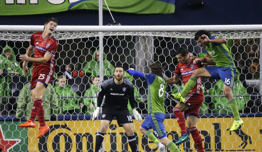 FC Dallas defender Walker Zimmerman, left, heads the ball away from the goal as goalkeeper Chris Seitz, second from left, looks on, and Seattle Sounders forward Nelson Haedo Valdez, right, tries to reach it, in the first half of an MLS soccer playoff match, Sunday, Oct. 30, 2016, in Seattle. (AP Photo/Ted S. Warren)
