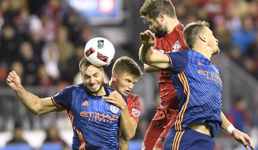 New York City FC defender Maxime Chanot (4), left to right, heads the ball away from Toronto FC defender Nick Hagglund (6) and Toronto FC defender Drew Moor (3) as New York City FC defender Frederic Brillant (13) defends during first half MLS soccer playoff action in Toronto, Sunday, Oct. 30, 2016. (Frank Gunn/The Canadian Press via AP)