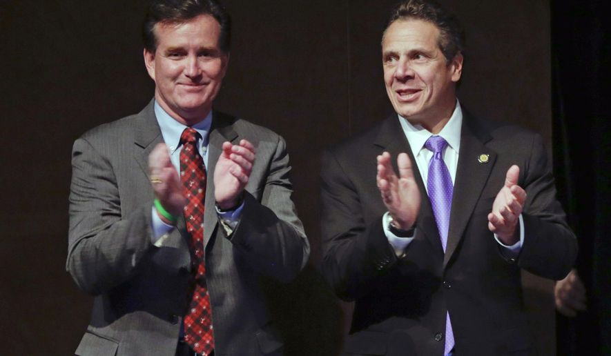 FILE - In this Dec. 10, 2015, file photo, Senate Majority Leader John Flanagan, R-Smithtown, left, and New York Gov. Andrew Cuomo applaud during an economic development awards ceremony in Albany, N.Y. This year's election will determine which party controls the New York state Senate. Republicans now control the chamber, but Democrats say GOP Presidential nominee Donald Trump's unpopularity in the state will help down-ballot Democrats. Flanagan warns that a Senate Democratic majority would become a tool of New York City liberals. (AP Photo/Mike Groll, File)