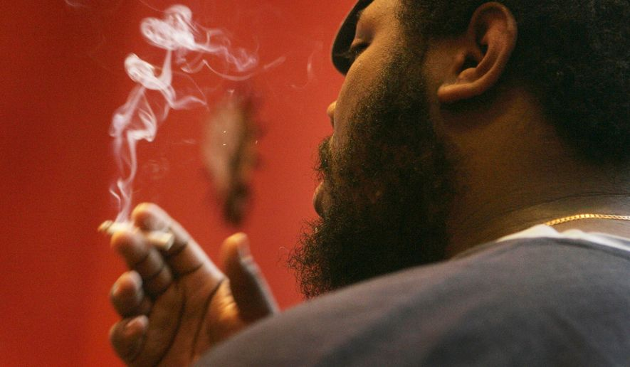 FILE - In this Jan. 23, 2008, file photo, Barrington Lloyd smokes a cigarette at a bar in St. Louis. Missouri's extraordinarily low tobacco tax will rise if at least one of two ballot measures passes in November 2016. (AP Photo/Jeff Roberson, File)