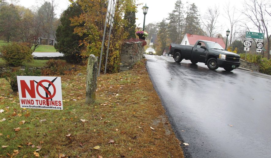 In this Tuesday, Oct. 18, 2016 photo, a yard sign opposing an industrial wind project sits at the side of the road in Grafton, Vt. Voters in Grafton and Windham are going to cast ballots Nov. 8 on whether to go forward with a plan for 24 turbines in the two communities. Developer Iberdrola Renewables is offering residents of the two towns direct payments if the project is built. (AP Photo/Wilson Ring)