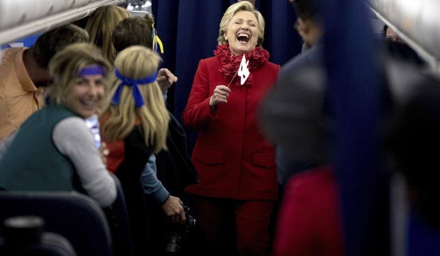 Democratic presidential candidate Hillary Clinton laughs with staff aboard her campaign plane at Cincinnati/Northern Kentucky International Airport in Hebron, Ky., Monday, Oct. 31, 2016, before traveling to Westchester, N.Y. on Halloween. (AP Photo/Andrew Harnik)