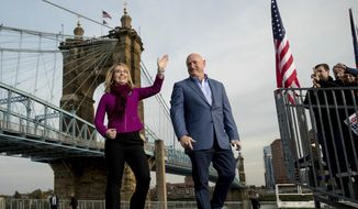 Gabby Giffords and her husband Mark Kelly, take the stage for a rally for Democratic presidential candidate Hillary Clinton at Smale Riverfront Park in Cincinnati, Monday, Oct. 31, 2016. (AP Photo/Andrew Harnik)