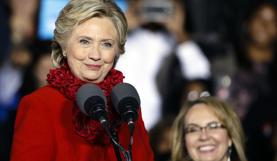 Democratic presidential candidate Hillary Clinton accompanied by former Arizona Rep. Gabby Giffords speaks during a campaign stop at the base of the John A. Roebling Suspension Bridge in Cincinnati, Monday, Oct. 31, 2016. (AP Photo/Matt Rourke)