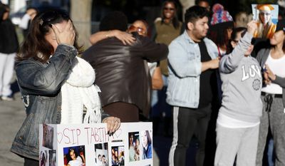 Friends and family of Tabitha Cruz, a woman killed at a Halloween party, become emotional during a vigil in Newburgh, N.Y., Monday, Oct. 31, 2016. Police have named a suspect they're seeking in connection with the Halloween party shooting that left Cruz and Omani Free dead and several other people wounded. (AP Photo/Seth Wenig)